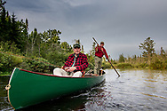 Brule River fishing guide Damian Wilmot poles upstream on the Brule with angler Matson Holbrook in a 1900-era Joe Lucius guide canoe Wilmot meticulously restored over the course of two years.