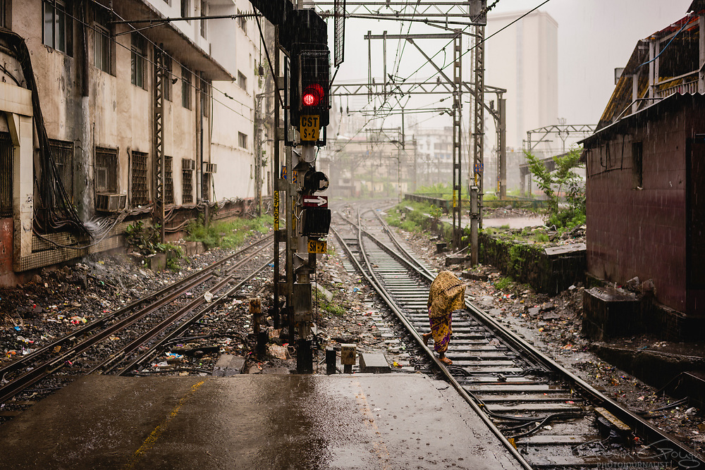 A woman covers her head as she crosses the railway tracks during a monsoon rain storm.