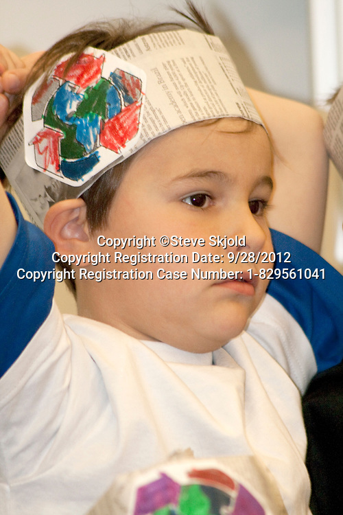Male first grade student wearing hat with recycle logo during a recycling program. Horace Mann School St Paul Minnesota MN USA