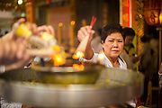 17 OCTOBER 2012 - BANGKOK, THAILAND:     A woman lights incense at Wat Mangkon Kamalawat, one of the largest Chinese shrines in Thailand, during the Vegetarian Festival. The Vegetarian Festival is celebrated throughout Thailand. It is the Thai version of the The Nine Emperor Gods Festival, a nine-day Taoist celebration celebrated in the 9th lunar month of the Chinese calendar. For nine days, those who are participating in the festival dress all in white and abstain from eating meat, poultry, seafood, and dairy products. Vendors and proprietors of restaurants indicate that vegetarian food is for sale at their establishments by putting a yellow flag out with Thai characters for meatless written on it in red.        PHOTO BY JACK KURTZ