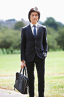 Portrait of young businessman carrying briefcase standing at park