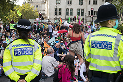 Metropolitan Police officers monitor climate activists from Extinction Rebellion occupying roads around Parliament Square during a Back The Bill rally on 1st September 2020 in London, United Kingdom. Extinction Rebellion activists are attending a series of September Rebellion protests around the UK to call on politicians to back the Climate and Ecological Emergency Bill (CEE Bill) which requires, among other measures, a serious plan to deal with the UK's share of emissions and to halt critical rises in global temperatures and for ordinary people to be involved in future environmental planning by means of a Citizens' Assembly.