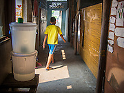 04 MARCH 2014 - MAE SOT, TAK, THAILAND: A boy walks through the hallway of the Sky Blue School. There are approximately 140 students in the Sky Blue School, north of Mae Sot. The school is next to the main landfill for Mae Sot and serves the children of the people who work in the landfill. The school relies on grants and donations from Non Governmental Organizations (NGOs). Reforms in Myanmar have alllowed NGOs to operate in Myanmar, as a result many NGOs are shifting resources to operations in Myanmar, leaving Burmese migrants and refugees in Thailand vulnerable. The Sky Blue School was not able to pay its teachers for three months during the current school year because money promised by a NGO wasn't delivered when the NGO started to support schools in Burma. The school got an emergency grant from the Burma Migrant Teachers' Association and has since been able to pay the teachers.    PHOTO BY JACK KURTZ