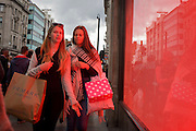 Tinted red from the Top Shop window display, two young women shoppers carry their purchases in Oxford Street, central London.