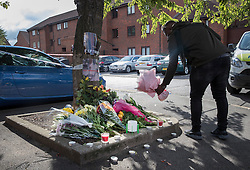 © Licensed to London News Pictures. 08/10/2016. London, UK. A man places flowers near the scene of a shooting in Eastney Road, Croydon. Police were called to reports of a man suffering a gunshot wound at 11.30 PM on Friday night. Officers from the Homicide and Major Crime Command are investigating after the man was pronounced dead at the scene.Photo credit: Peter Macdiarmid/LNP