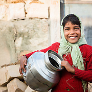 Portrait of girl carrying water pot in village of Chandelao, Rajasthan