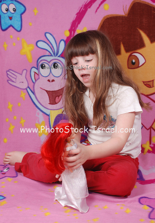 Young girl of five plays with a doll