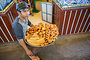 "30 JANUARY 2013 - PHNOM PENH, CAMBODIA:  A bakery vendor in the Central Market in Phnom Penh. The Central Market (""Psah Thom Thmey"", ""New Grand Market""), is a large market constructed in 1937 in the shape of a dome with four arms branching out into vast hallways with stalls of goods. It opened in 1937, and was the biggest market in Asia at the time; today it still operates as a market. It was renovated from 2009 to 2011.     PHOTO BY JACK KURTZ"
