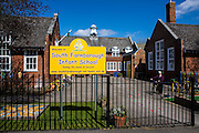 The entrance sign to South Farnborough Infant School, Hampshire, UK. A woman pushes her bicycle across the playground to leave the school.