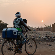 A woman and child cycling along a thoroughfare at sunset in the informal settlement of Zongo in Burkina Faso's capital, Ouagadougou, on 17 February 2016.