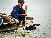 06 OCTOBER 2015 - BANGKOK, THAILAND:     A spotter on a salvage diver's boat paddles down the Chao Phraya River in Bangkok. Divers work in two man teams on small boats in the Chao Phraya River. One person stays in the boat while the diver scours the river bottom for anything that can be salvaged and resold. The divers usually work close to shore because the center of the river is a busy commercial waterway with passenger boats and commercial freight barges passing up and down the river all day long. The Chao Phraya is a dangerous river to dive in. It's deep, has large tidal fluctuations, is fast flowing and badly polluted. The divers make money only when they sell something.    PHOTO BY JACK KURTZ