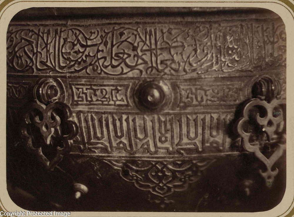 1865<br /> This photograph of a detail of a ritual basin in the interior of the mausoleum of Khodzha Akhmed Iassavi in Yasi (present-day Turkestan, Kazakhstan) is from the archeological part of Turkestan Album. The six-volume photographic survey was produced in 1871-72 under the patronage of General Konstantin P. von Kaufman, the first governor-general (1867-82) of Turkestan, as the Russian Empire&rsquo;s Central Asian territories were called. Yasi is associated with the Sufi mystic, Khodzha Akhmed Iassavi (1103-66), whose great reputation led Timur (Tamerlane) to construct a memorial shrine (khanaka) at his grave site. Built in 1396-98, the mausoleum displays features of Timurid architecture, then at its height in Samarkand. This view shows part of a large bronze ritual water basin, stated by an inscription on the basin to have been donated by Tamerlane. The basin is elaborately decorated with botanical figures and Perso-Arabic inscriptions. At the top is a band of Naskh script intertwined with a tendril pattern. Below this band are decorative bronze fittings and another inscription, in block letters. On the curved surface at the bottom of the photograph is an arabesque figure. The height of the basin is about one meter.