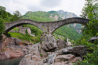 The old roman bridge spanning the river in Valle Verzasca, Ticino, Switzerland.  The imposing mountains and the church in the background add color and depth to this photo.