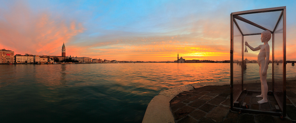 "A glorious sunrise over the San Marco basin on a cold december morning, after a stormy and rainy night. ""Boy with frog"" is a sculpture in white steel of the LA based artist Charles Ray. It's prominently situated on the very tip of the Punta della Dogana, exactly where the Grand Canal, the Giudecca Canal and the San Marco basin converge, and it was placed here at the beginning of June 2009 for the opening of the new exhibition center at the Dogana. I took this picture at dawn at the beginning of December. It had been rainy all the day and the night before, but the sky finally broke just in time for putting on stage one of the best sunrise I have ever witnessed. This is a stitch of 8 vertical frames, covering a field of view of nearly 180°"