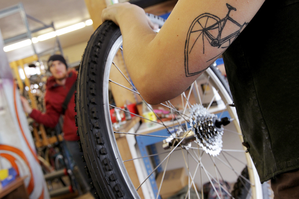 Assistant manager Alice Brandt, 23, right, talks with a customer as she works on a bicycle at Express Bike Shop in St. Paul, Minnesota.  Brandt oversees youth apprentices who work part time at the shop where they learn mechanical skills related to fixing bicycles, as well as customer relation and entrepreneurial skills..