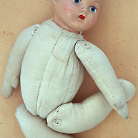 Vintage baby doll with boyish face and padded fabric body lying naked on antique paper