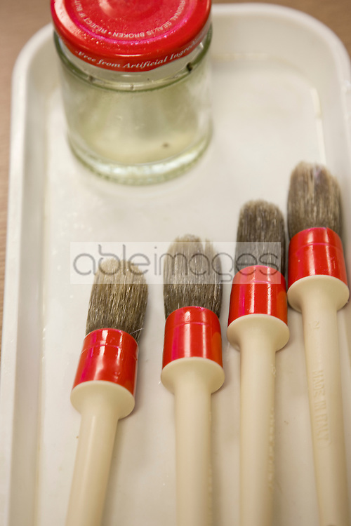 Close up of a set of sash brushes and glass jar on a white tray