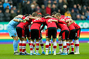 Southampton huddle in front of the Rainbow Laces advertising ahead of the Premier League match between Newcastle United and Southampton at St. James's Park, Newcastle, England on 8 December 2019.