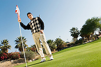 Young Man on Putting Green Holding Golf Flag