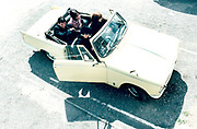 Four young people sitting in a convertible car.