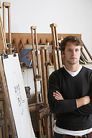 Artist standing by charcoal portrait in studio