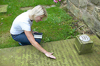 lady looking at details on a gravestone