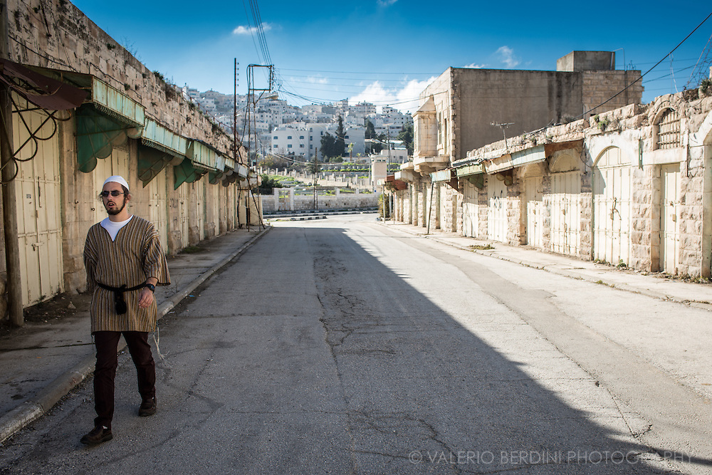 A jewish settler walks a desolate street of Area H2 in Hebron. The whole zone is under IDF control and Arabs are banned to walk here. Non muslims are allowed upon showing a western passport at a checkpoint. Settlers are often unwelcoming and hostile to foreign visitors.