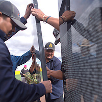 Eric Jim, left, and Michael Town, middle, help assemble the Moving Vietnam Memorial Wall at the softball field at Chinle High School in Chinle Thursday. The 70 panels bear the names of all Vietnam veterans who were either killed in action or missing in action and will be on display open to the public through Monday.