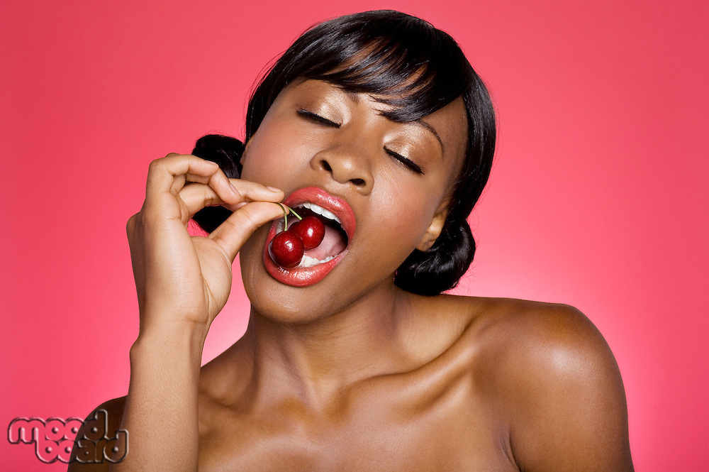 Close up of woman eating cherry with eyes closed