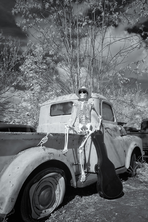 Traveling skeleton musician with a guitar case sits waiting outdoors on an old Dodge pickup truck, black and white infrared photograph.