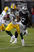 Green Bay Packers rookie cornerback Jaire Alexander (23) is chased by Oakland Raiders wide receiver Dwayne Harris (17) after intercepting a second quarter pass that gives the Packers the ball at their own 7 yard line and stopping a deep Raiders drive during the 2018 NFL preseason week 3 football game against the Oakland Raiders on Friday, Aug. 24, 2018 in Oakland, Calif. The Raiders won the game 13-6. (©Paul Anthony Spinelli)