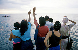 Lourdes Rios, her sister and other family members gather at the waters edge to wave one last goodbye to their loved ones setting sail for the United States. In the summer of 1994 Cubans once again began taking to the water, attempting to escape the oppression of Fidel Castro's government. Many tried, but few made the treacherous journey across the Florida Straights. (Photo © Jock Fistick)