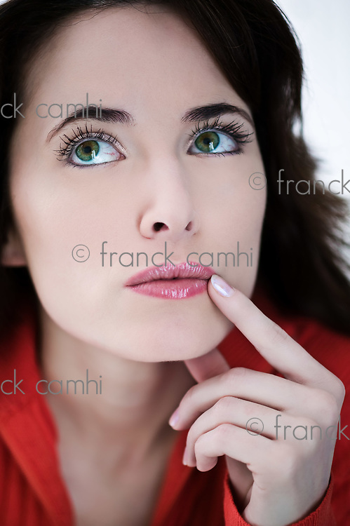 studio portrait on isolated background of a beautiful  expressive woman thinking