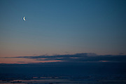 The moon rises over Arctic Sea Ice, Fram Strait, between Greenland and Svalbard, September 2009. In August 2012, Arctic sea ice hit a record minimum - this will affect weather and the global climate, as the ice cap reflects much of the sun's solar energy back into to space. With sea ice melting away, the dark water below absorbs more solar energy, which in turn causes more melting.
