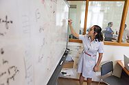 A young woman writes on a whiteboard, Hanoi, Vietnam, Southeast Asia