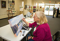 BJ Eckardt paints the view Breck Shore on Lake Winnisquam during the NH Open Doors in conjunction with Lakes Region Art Association at the Tanger Outlet on Sunday afternoon.  (Karen Bobotas/for the Laconia Daily Sun)