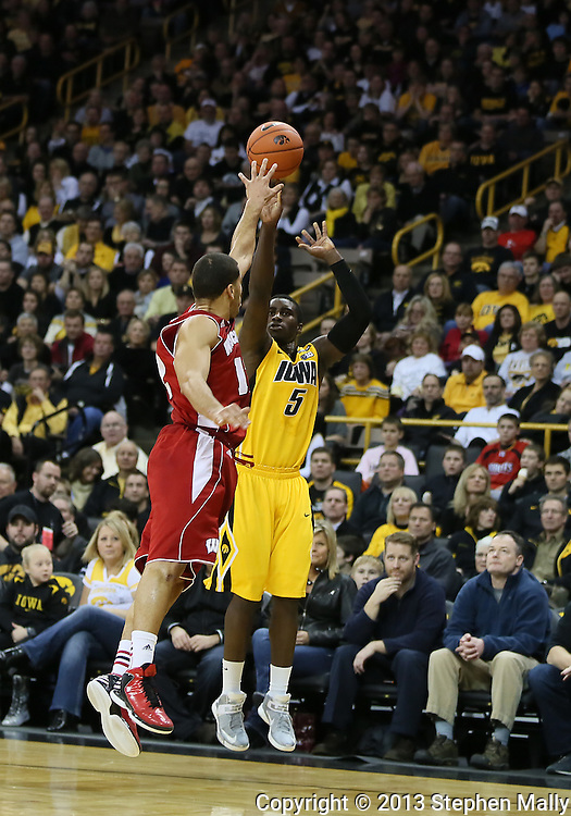 January 19 2013: Iowa Hawkeyes guard Anthony Clemmons (5) puts up a shot as Wisconsin Badgers guard Traevon Jackson (12) defends during the first half of the NCAA basketball game between the Wisconsin Badgers and the Iowa Hawkeyes at Carver-Hawkeye Arena in Iowa City, Iowa on Sautrday January 19 2013. Iowa defeated Wisconsin 70-66.