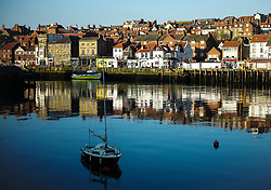 © Licensed to London News Pictures. <br /> 09/04/2017<br /> Whitby, UK. <br />  <br /> A yacht is moored in the harbour as sunlight shines off buildings in Whitby in North Yorkshire. <br /> <br /> <br /> Photo credit: Ian Forsyth/LNP
