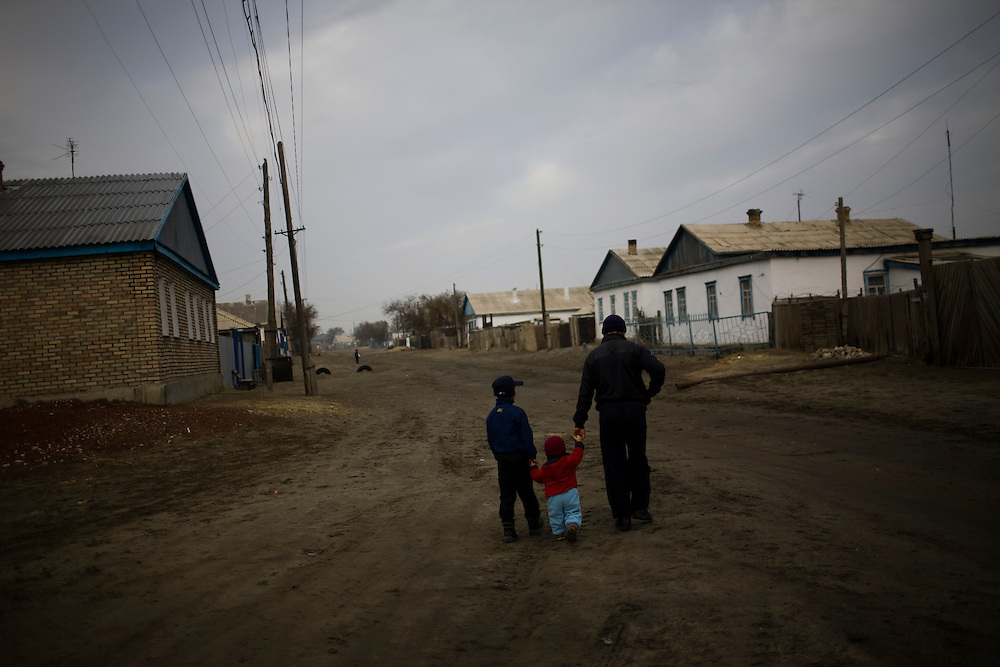 CREDIT: DOMINIC BRACCO II..SLUG:PRJ/KAZAKHSTAN..DATE:11/4/2009..CAPTION:A man and to children walk down a dusty road in Aralsk, Kazakhstan on November 4, 2009. According to locals the city was much greener when the sea was at its port. ..Aral Sea Overview: ..During the 1960s the USSR began irrigating the waters of the Aral Sea in southern Kazakhstan to combat their growing food crisis. The Soviets severely miscalculated and water began receding quickly from the port cities. The waters continued to recede. By 2000 the water was 80 km away from the city of Aralsk, a main seaport in Kazakhstan. In 2005 with help from the World Bank, construction began on a 13km dike that locals hoped would bring the waters back to their original shores. The project raised water quality and fishing was able to resume, however four years after completion of the dike the water is still 50km from Aralsk's port. Locals seem mixed on the possibility of the sea returning after more than 40 years without the sea. Fishermen from Aralsk make a three-hour path through soft desert road along the former seabed. The only source of income for many is cattle, horses, and camels, which have, began to overgraze the areas of the former seabed and surrounding desert. Because of this nutrient rich topsoil is lifted by the wind and the process of desertification continues.  .