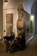 Muslim visitors pose for a selfie beneath the giant Assyrian Winged human-headed lion from about 865-860BC from the ancient city of Numrud. This protective spirit guarded the entrance into what may have been a banquet hall.