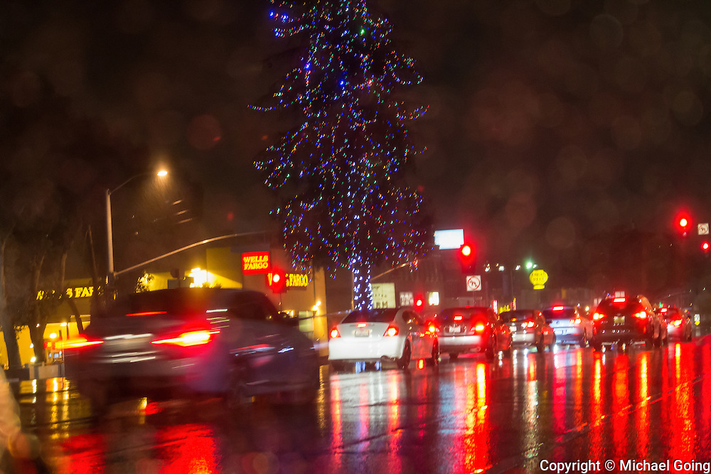 night shot in the rain of rain drops on car windshield with cars and light reflections on the street