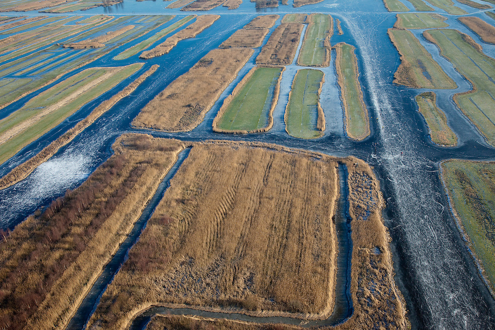 Nederland, Noord-Holland, Zaandam, 10-01-2009; Polder Oostzaan met het Oostzanerveld, vormt onderdeel van het Nationaal Landschap Waterland (Laag Holland); veenweidegebied, ontstaat door afgraven van turf; (nog) in gebruik voor veeteelt door 'waterboeren', bedreigd gebied;.the landscape is the result of diging up the peat in the past; still in use by cattle farmers (cows, dairy-catle);.schaats, schaatser, schaatsen, ijs, ijspret, pret, ijsbaan, natuurijs, schaatsen rijden, winter, koud, vriezen, min nul, beneden nul, onder nul, koud, celsius, skating, ice skating, ice, fun, natural, skate, snow, cold, freezing, minus zero, below zero, cold, winterlandschap, winter landscape, tocht, toertocht;. .luchtfoto (toeslag); aerial photo (additional fee required); .foto Siebe Swart / photo Siebe Swart
