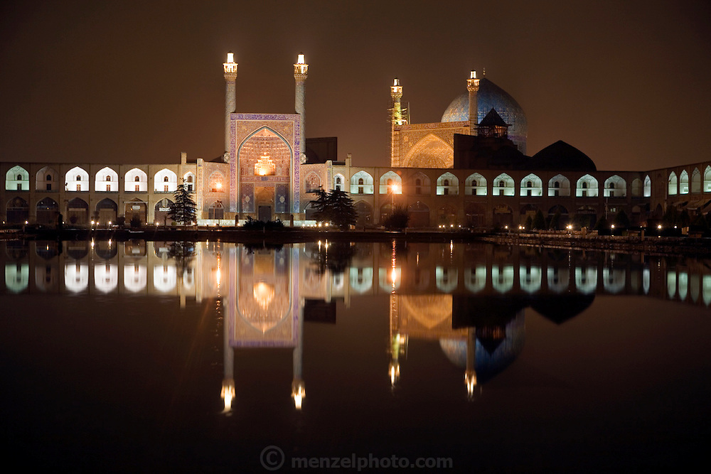A view of the magnificently tiled Masjed-e Imam (Royal Mosque) and its reflection at night in Imam Square, in the city of Isfahan, Iran. The square, also referred to as Emam Square was built by the Safavid ruler, Shah Abbas 1, as part of the renovation of the central square of Isfahan. The architect was Ostad Abu'l-Qasim.  (Imam Square is also called Naghsh-i Jahan Square).
