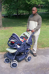 Young father walking through park pushing baby in pram,
