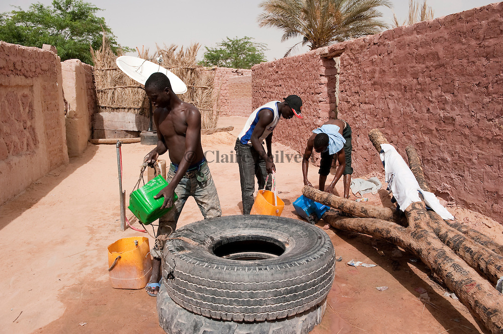 Two young African migrants drawing water from a well in a ghetto in Dirkou.