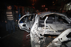 ©Licensed to London News Pictures. 27/12/2011, Gaza. Palestinians look at a car damaged after a reported Israeli air strike in the northern Gaza Strip December 27, 2011. Photo Credit: Yasser Fathi /PNC/LNP