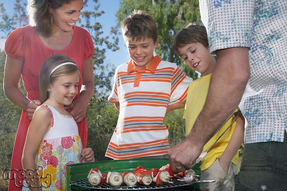 Family with three children (6-11) grilling in garden