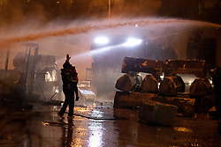 © Licensed to London News Pictures. 25/01/2020. Beirut, Lebanon. A demonstrator with a young child stands in front of a water cannon as part of a protest on Riad Al Solh Square, Beirut, outside the Grand Serail (Government Palace), where it is reported that Lebanese Prime Minister Hassan Diab is living. Today marks the 100th day of demonstrations in Lebanon<br /> . Police used tear gas and water cannon to disperse the anti-government demonstrators, who are campaigning against government corruption and economic crisis. Photo credit : Tom Nicholson/LNP