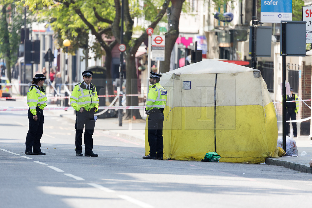 © Licensed to London News Pictures. 22/05/2018. London, UK. Police at the crime scene cordon next to the forensic tent in Upper Street, Islington which remains closed this morning. Police were called at approximately 18:30hrs on Monday, 21 May to reports of a man suffering stab injuries after being attacked in Upper Street.<br /> Officers and London Ambulance Service attended. The man was pronounced dead at the scene. Photo credit: Vickie Flores/LNP