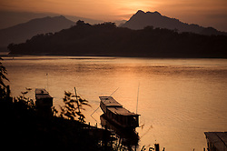 Few barges are moored along the mekong river at sunset. Luang Prabang, Laos, Asia